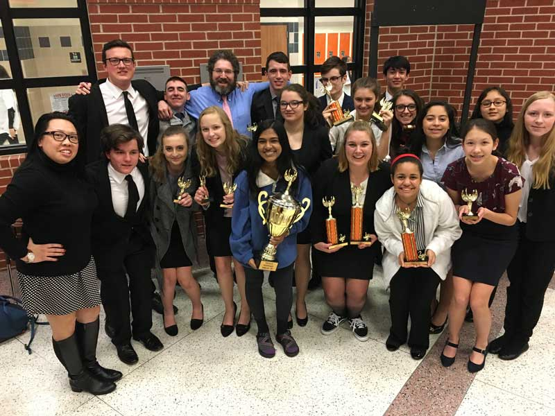 The speech and debate team displaying their trophies after a tournament.